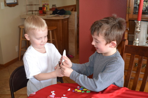 Bennett (right) showing Thomas how the hole puncher works.