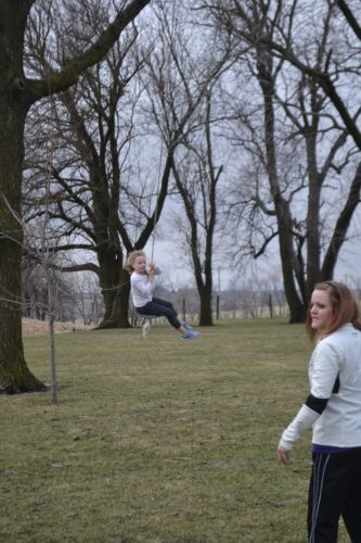 Ava gliding through the air with hard pushes from Aunt Jenny